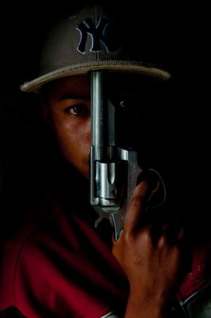 """I continue till the end. I kill or I get killed"". A young Colombian from Medellín poses holding his gun."