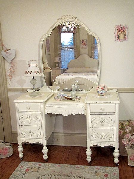 This vanity with its large mirror is beautifully designed with lots of love. All the lovely appliques and scrollwork enhance its gracefulness. The vanity is refinished a linen white and distressed. The six drawers feature the original hardware painted the same white.