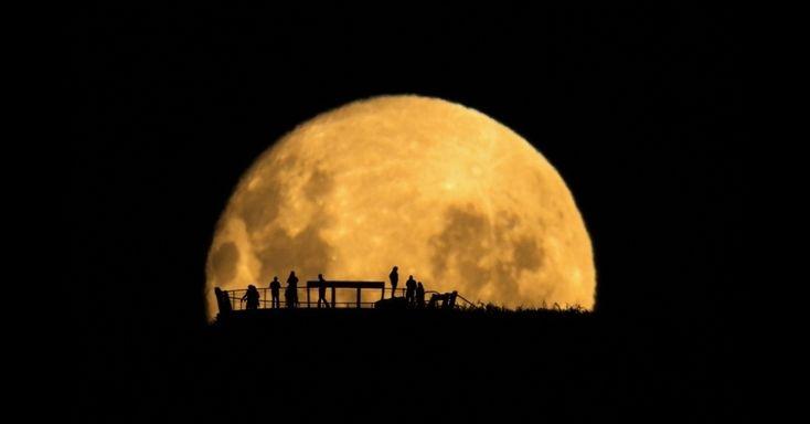 """Moon Silhouettes de Mark Gee venceu o prêmio especial """"Pessoas e Espaço"""". Esta é uma foto da silhueta de pessoas contra uma lua crescente. Ao fotografar de uma grande distância pessoas em um observatório, o fotógrafo enfatizou o quão pequeno somos em comparação à grandeza do nosso satélite natural, a Lua."""