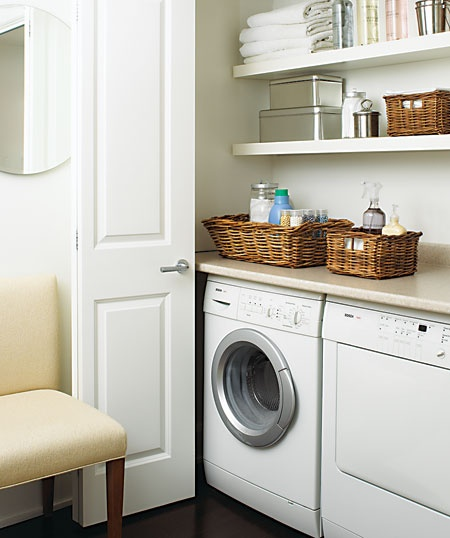 Bi-fold doors conceal a washer dryer with a counter, and open shelving.