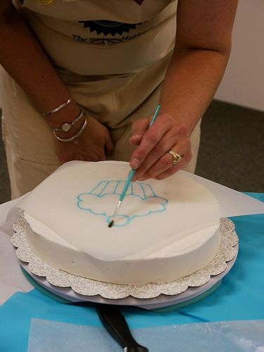 using parchment paper and piping gel to make a template on your cake...and how to use parchment paper to smooth surface of cake.