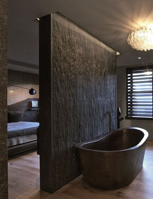 Black slate wall divider bathroom. Black bath tub