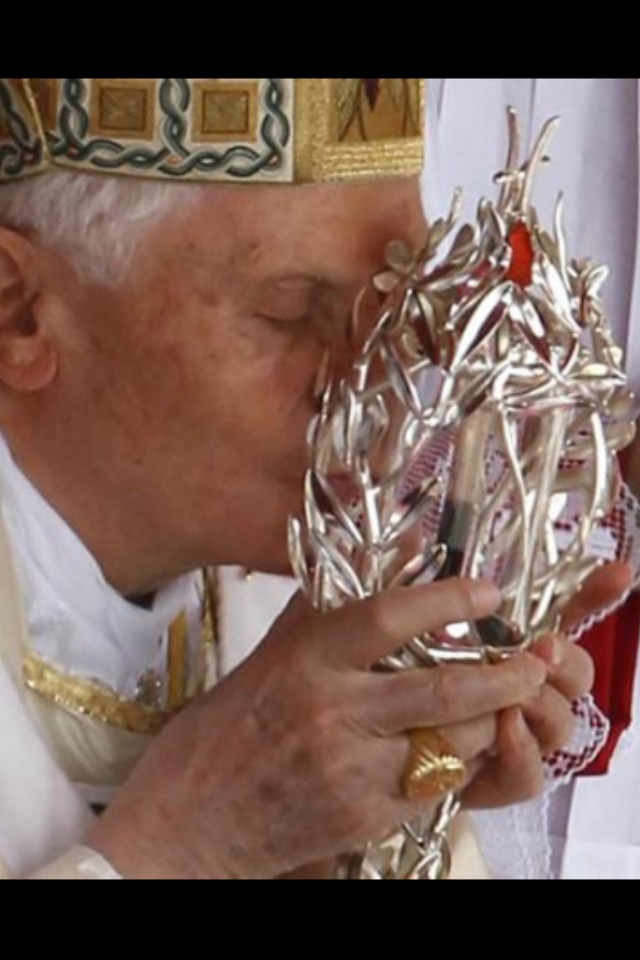 Pope Benedict kissing reliquary containing vial of blood from Pope John Paul II.