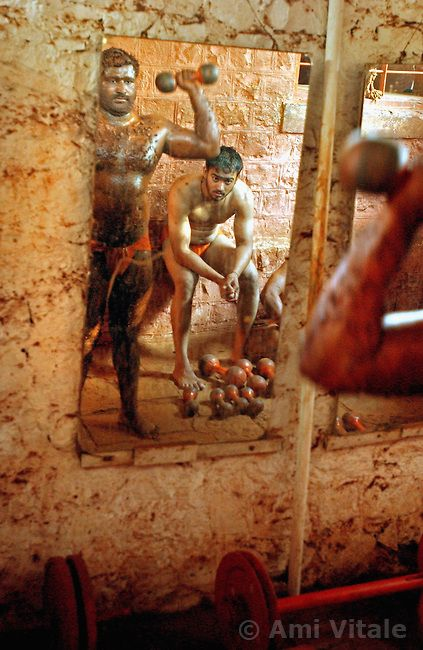 """KOLHAPUR, INDIA - MARCH 22: Indian men practice the three thousand year old sport known as """"Kushti"""", a form of wrestling, in its traditional..."""
