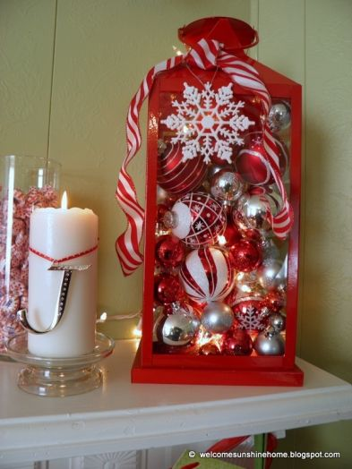 Lantern with peppermint-like ribbons and ornaments (could also use a large jar). Love the lights mixed in and the snowflake ornament on the front.