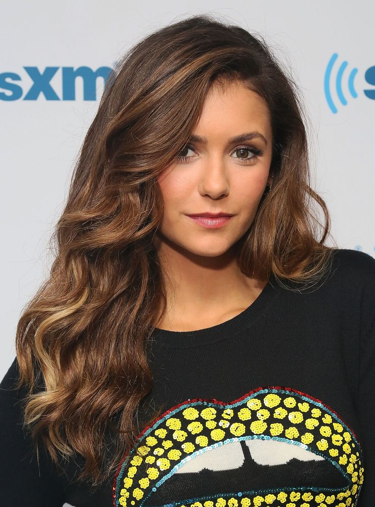 A flush of pink to the cheeks, rosy lips, and softly smoky shadow—Nina Dobrev created a feminine, romantic look.