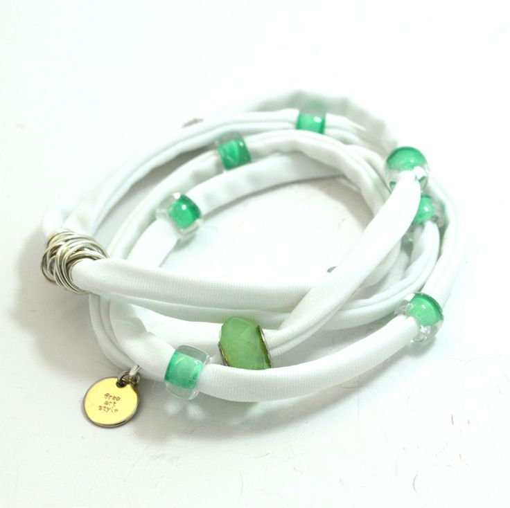 Douple lycra cord in white embellished with unique green glass beads and handmade silver wire detail. Length approx. 40 cm. Each. Two (2) turns each round the wrist. Adjustable bracelet, fits to all wrist sizes. Comes in a gift box.