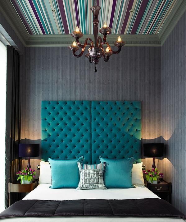 Loving that striped ceiling, chandelier, tufted headboard.