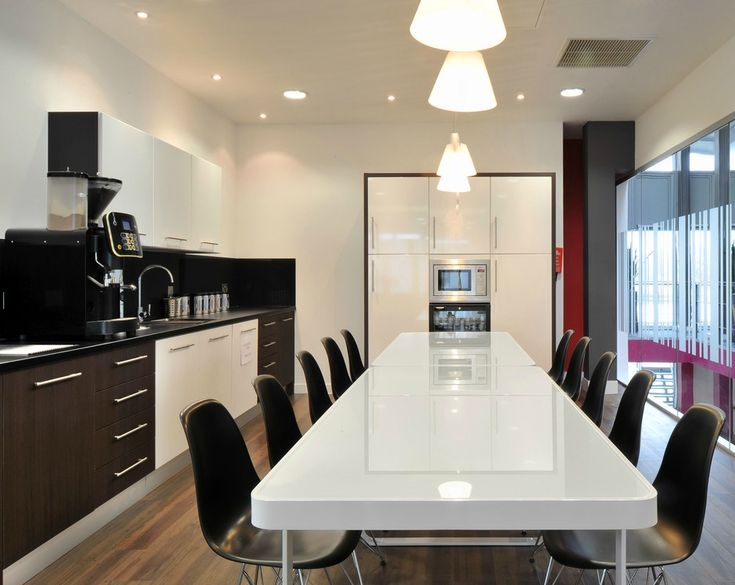 Office Kitchens >> Workplace Dining >> This stylish office kitchen dining space uses a selection of high gloss finishes to create a great looking workplace kitchen. Dark wood and white kitchen units are combined with a black kitchen worktop and black splashback. A gloss white dining table is teamed with black dining chairs and a built in microwave and drinks fridge. See more of this Cambridge office design and build project on our website: