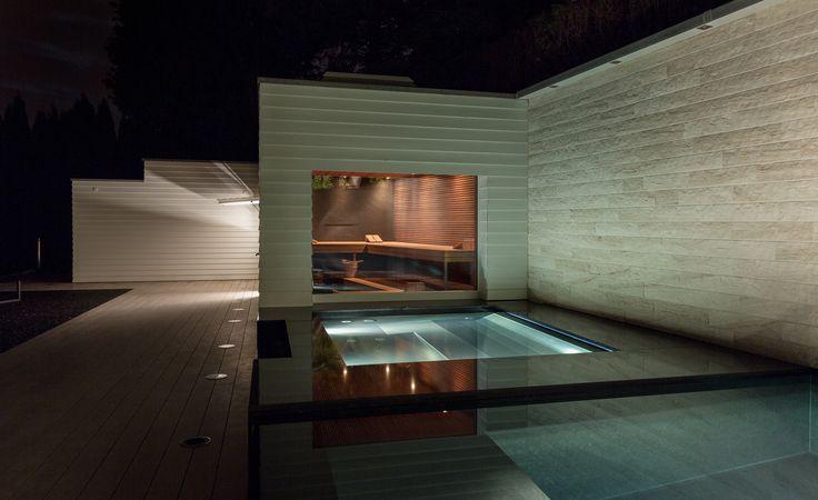 Der Naturstein Whirlpool liegt zwischen dem Pool und dem Gebäude der Sauna.