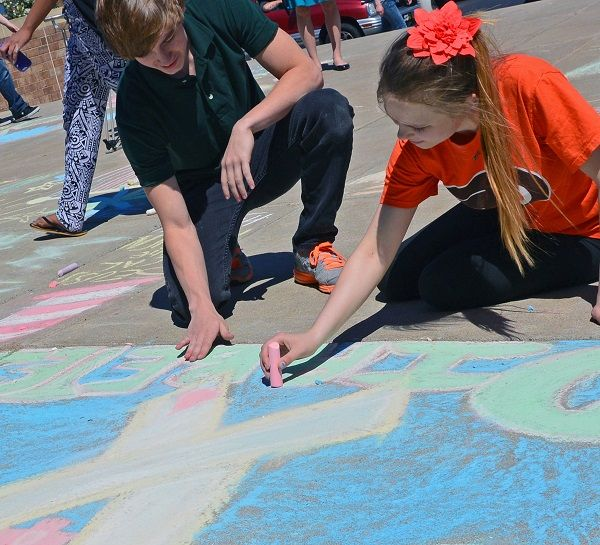 Pennridge High School seniors Max Susson with Kirsten Pearce, whose dad has diabetes, created a chalk art banner about diabetes. News-Herald photo — DEBBY HIGH
