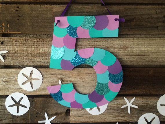 ¡Colgar este signo adorable de la sirena inspirado partido número en tu próxima fiesta! A ver como escamas de pescado. ¡Utilizarla como una señal de puerta o colgar en una mesa de regalos! No se incluyen los dólares de arena-vea por favor comprar separado Listado ** Colores: Tonos de púrpura, azul y verde azulado con algún brillo. Tamaño: Aprox. 9 de ancho por 11 alto. Cada número puede variar de tamaño debido a la forma del número, por ejemplo, el número 1 no será tan amplio como este…