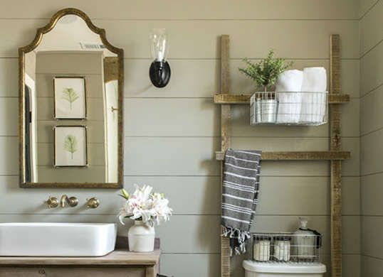 Creative shelving can go a long way in a small half bath. This ladder shelf houses spaces for bathroom necessities to sit, while adding a rustic touch to the room.