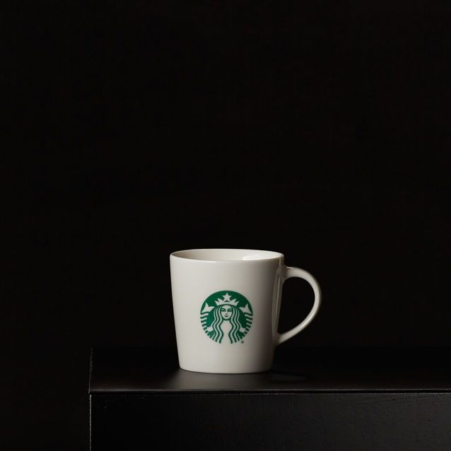 A demi-sized ceramic coffee mug in white with a green Siren logo. Part of the Dot Collection.