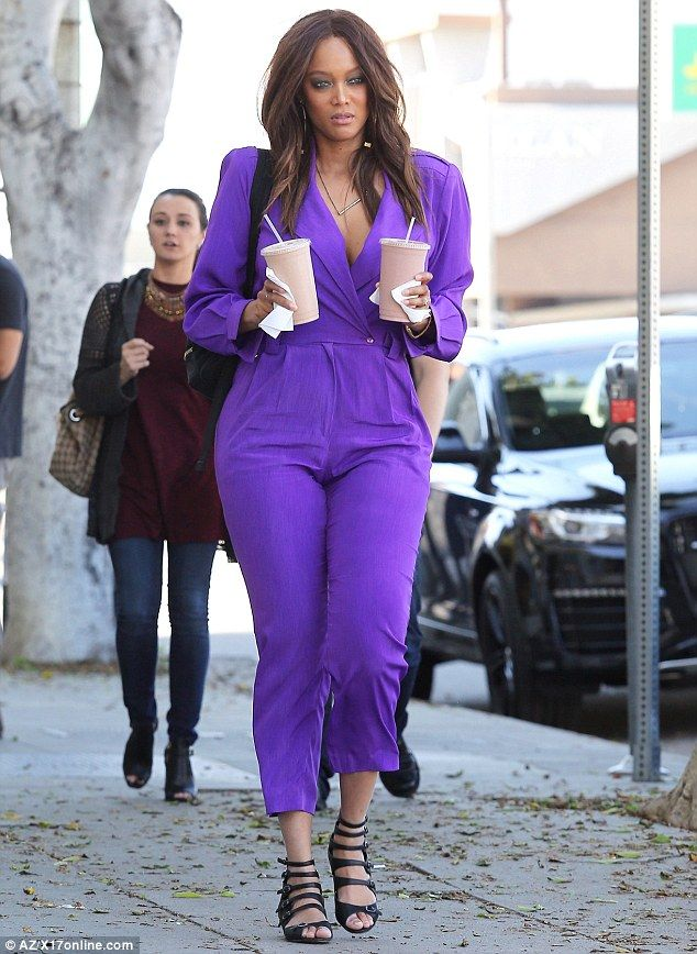 No shrinking violet: Tyra stood out in a bright purple jumpsuit, which left her ample cleavage on display