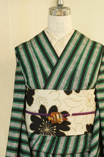 黒のネップがアクセントになったナチュラルグレーの地に、緑と黒のコントラストもスタイリッシュに、大胆なストライプが織り出されたシルクウール紬風単着物です。