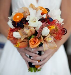 Edible Wedding Bouquet... This bridal bouquet uses pincusshions, orange slices, white cattleya orchids, white tulips, orange roses, celosias and brown cymbidiums. Perfect for a fall wedding.