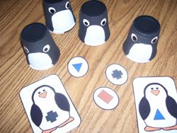 "Here's a shape matching game where students match penguin shapes to ""eggs"" hidden under penguin cups."