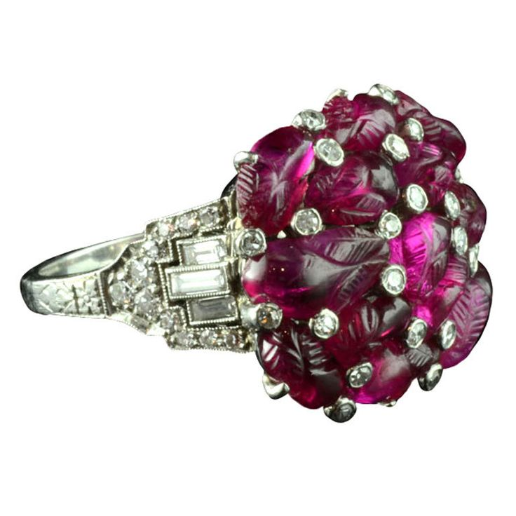 Art Deco ruby and diamond cluster ring, circa 1930.  Unusual cocktail ring designed as a cluster of rubies each carved into the shape of leaves and buds in between diamond collets.