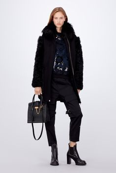 Louis Vuitton Women's Fall-Winter 2017 Collection by Nicolas Ghesquière - Look 7 This look embodies the collection's strong fur theme, along with its signature masculine/feminine vibe. An easy and chic parka in cashmere and fur is worn with an on-trend jersey sweatshirt - influenced by American sportswear - and high-waisted wollen pants with a low crotch.