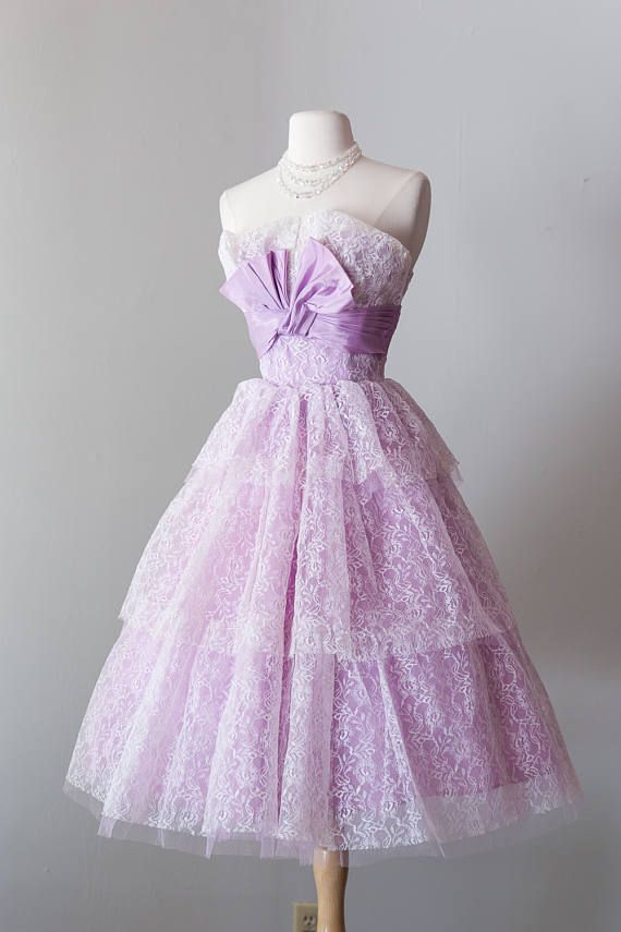 How darling is this lilac lace cupcake dress we found?! We know—its one of a kind. Tiered lace obscures the neckline of the boned bodice, and is then wrapped in a taffeta, pleated ribbon. You get not one but TWO eye-catching bows on this baby: one in the front, creating a lovely V at the bust, and another in the back, partially hiding the original metal zipper. Wed recommend wearing a petticoat with this for full 50s effect, but if you so choose to forgo one, this skirt includes FOUR LAYERS…
