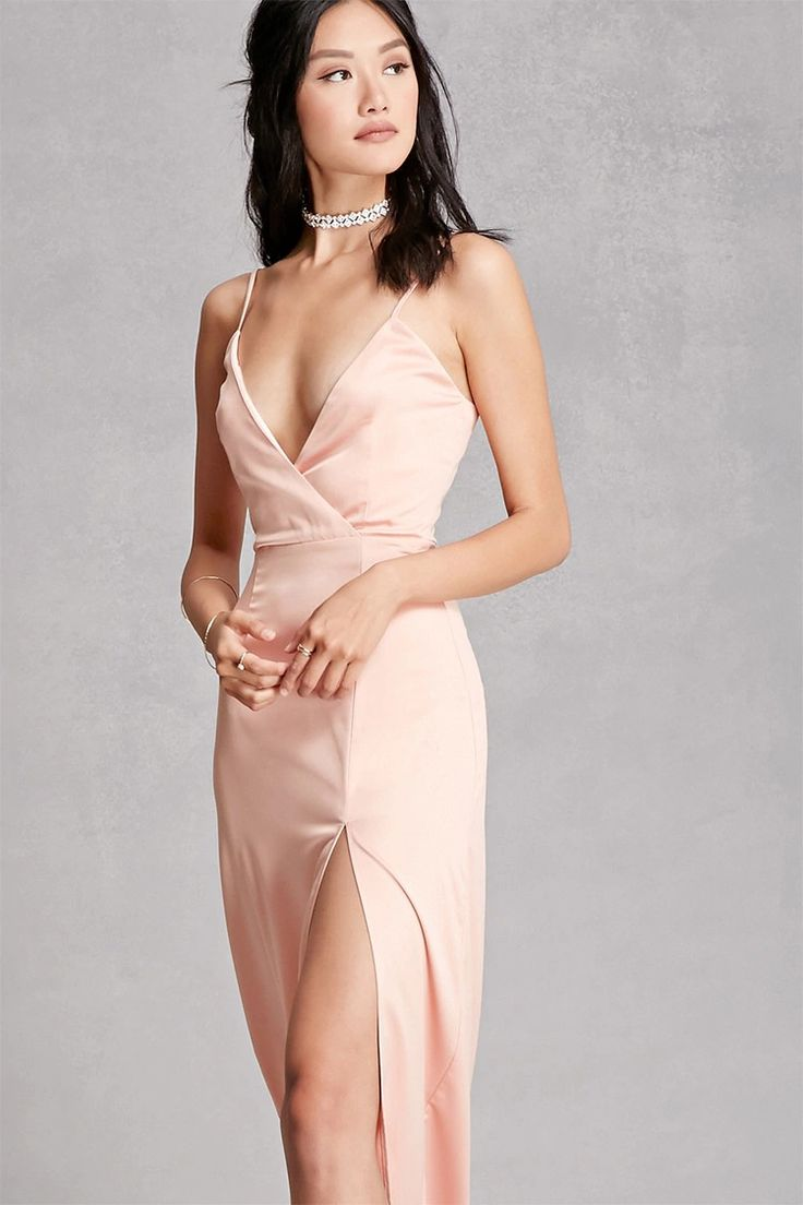 A satin maxi cami dress by Girl In Mind™ featuring a surplice front, adjustable straps, a concealed back zipper, and an asymmetrical side slit.