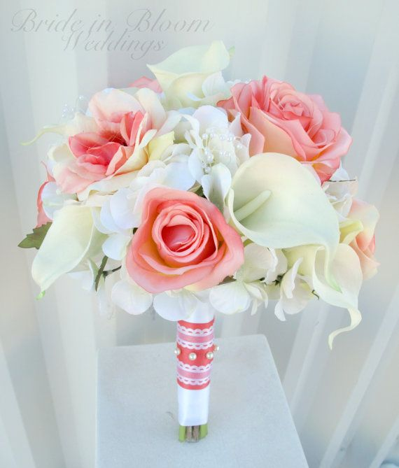 This elegant wedding bouquet is designed with 12 white real touch calla lilies, pretty coral roses, on a bed of creamy white hydrangea, pearl loops throughout. Handle treatment is wrapped with white & coral satin ribbon with a white lace sash & pearl pins to finish. Pictured bouquet measures: 10 ( 25 cm ) wide x 12 ( 30 cm ) tall. Coordinating boutonniere: https://www.etsy.com/listing/287592677/wedding-boutonniere-white-calla-lily?ref=shop_home_active_1…