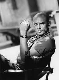 Yul Brynner. Looks like an early watch advertisement but I think he's just been snapped having his coffee break. I wonder what watch he's wearing though....any ideas?