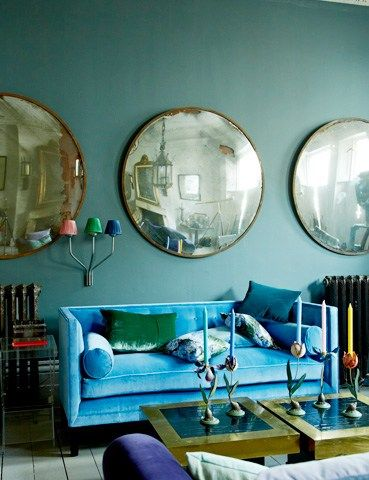 Convex mirrors, lovely wall paint color and glorious couch