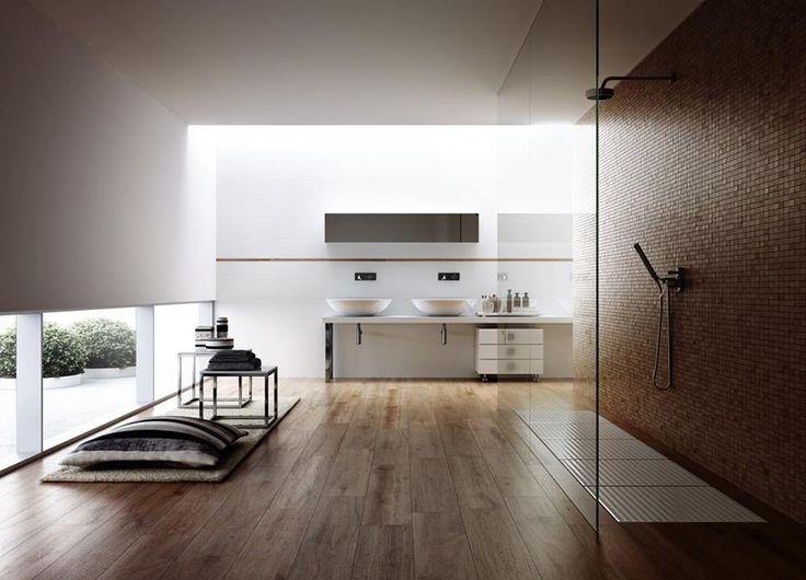 Il pavimento in legno conferisce a questo bagno un moderno fascino rustico. Il mosaico che riveste la doccia ha un colore simile alla venatura del legno e offre un tocco di colore al bagno interamente bianco