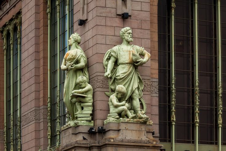 Statues signifying strength and learning on an historic building facade above the Neva River in St. Petersburg, Russia.