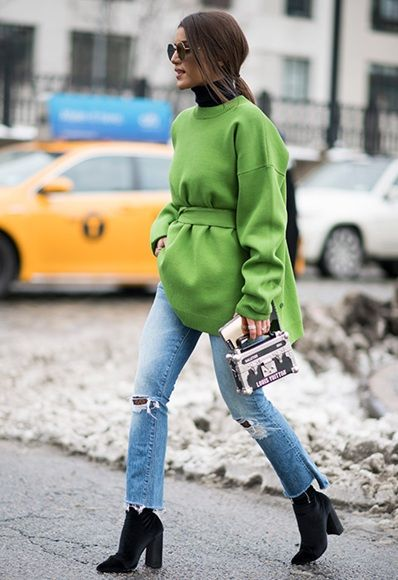 A fashion week attendee wearing a green knit with ripped jeans and fishnets | ASOS Fashion & Beauty Feed