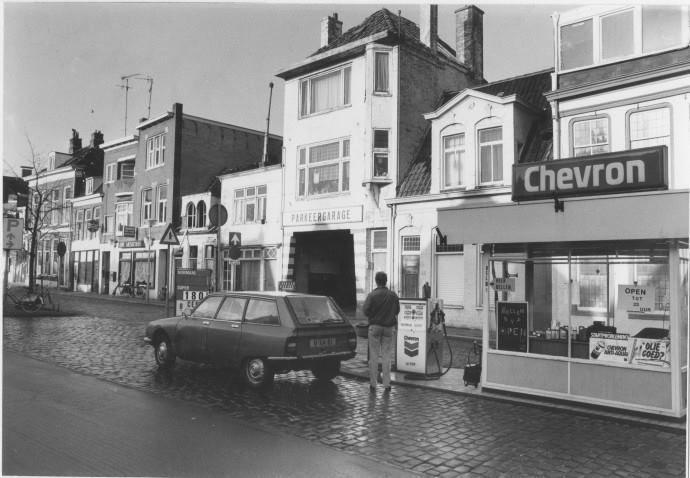 Het Kattendiep aan de noordzijde met een Chevron benzinepomp, Citroën parkeergarage (nummer 36) en café De Drie Musketiers (nummers 28 en 30).1984 - Foto's SERC