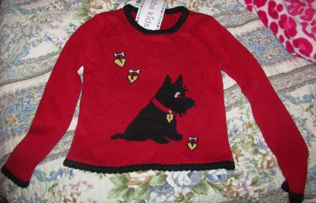 This adorable girl's sweater would be perfect for Valentine's Day.     Color is true red.     Size is mediium 5/6     Front features a Scotty Dog. It has yellow hearts attached to white bones.  Trimmed in black.     Brand is Kobe Kids     55% ramie     45% cotton     New with tags