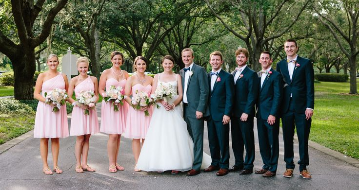 the wedding party poses under the canopy of live oak trees. the bridesmaids in knee length blush pink dresses carried bouquets of cafe au lait dahlias, white ranunculus, white stock, juliette garden roses, dusty miller and seeded eucalyptus. the groomsmen wore navy suits, madras plaid bow ties and boutonnieres of pink ranunculus.