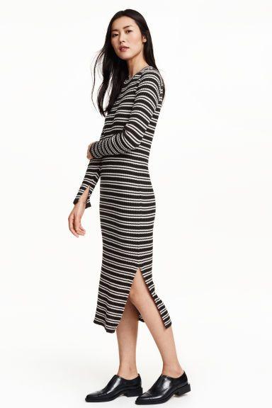 Вязаное резинкой платье: Платье длиной до середины икры, связано резинкой из смесового хлопка. Облегающая модель с длинным рукавом.