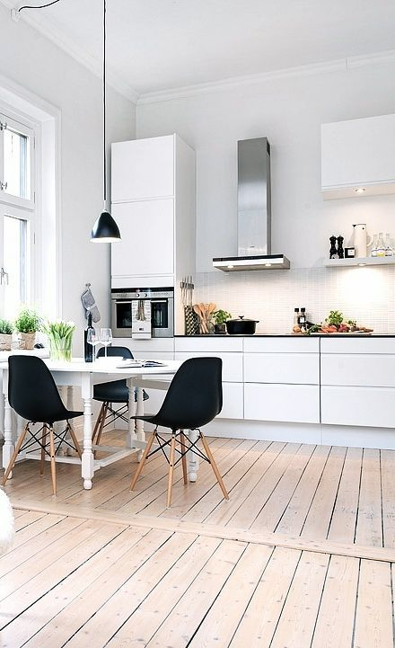 Bright, monochrome, Scandinavian kitchen with whitewashed walls, rustic wood floors, and black accents