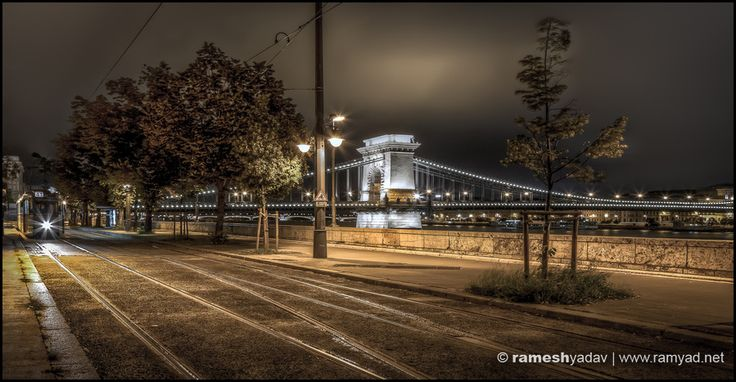 tram stop and chain bridge at night