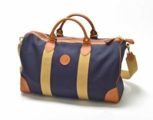 Blue Canvas Holdall A smart and stylish holdall designed to comply with current IATA carry-on regulations; ideal for long weekends, overnight trips and other shorter journeys. Features the Oxford University Logo on the front, an exterior zipped pocket, saddle stitched leather handles, leather reinforced corner panels and an adjustable and detachable shoulder strap.  Hand crafted in Cumbria.