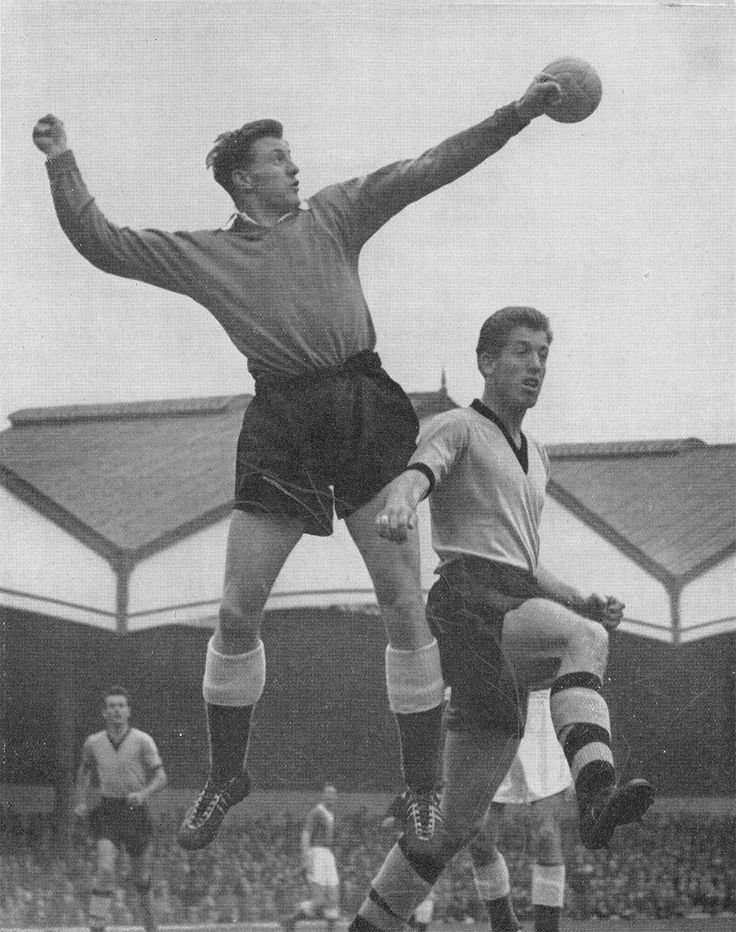 1st September 1956. Everton goalkeeper Jimmy O'Neil punching clear under pressure from Wolverhampton Wanderers forward Peter Broadbent, at Molinuex.