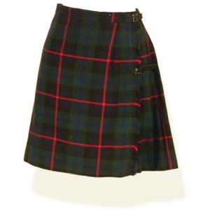 Tartan Skirt and always a large gold safety pin closer to the bottom of the skirt, kr
