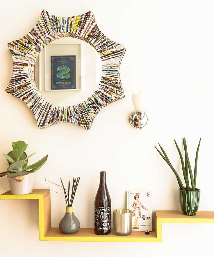 A yellow shelf with plants and objet, and a mirror on the wall above framed with magazines.