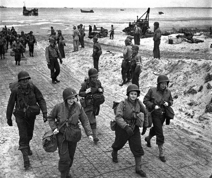 U.S. nurses walk along a beach in Normandy, France on July 4, 1944, after they had waded through the surf from their landing craft. They are on their way to field hospitals to care for the wounded allied soldiers.
