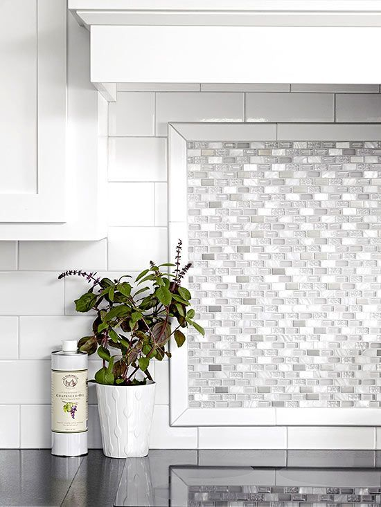 Mother-of-pearl tiles above the range add luster and light to the plain white subway tiles. The small tiles help to break up the large expanse of wall and add a fresh look to the kitchen.