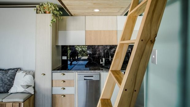 The compact kitchen includes a vertical sliding pantry at left, and a variety of timber veneers.