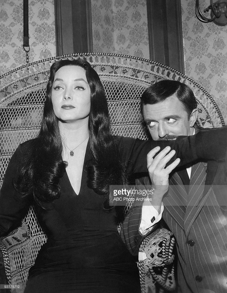 The Addams Family - 'Cousin Itt and the Voc. Counselor'- Season One. Gomez ( John Astin) Kisses up Morticia's ( Carolyn Jones) arm as she sits in a large wicker chair., gazing into the distance.,