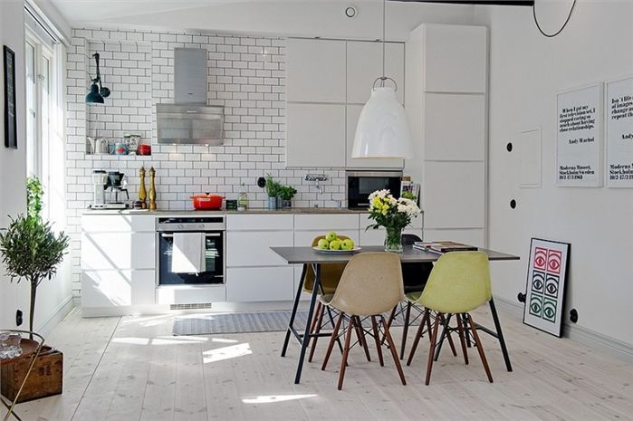 White subway tiles, pastel Eames chairs, all bright and open. If this kitchen aint Swedish then neither am I