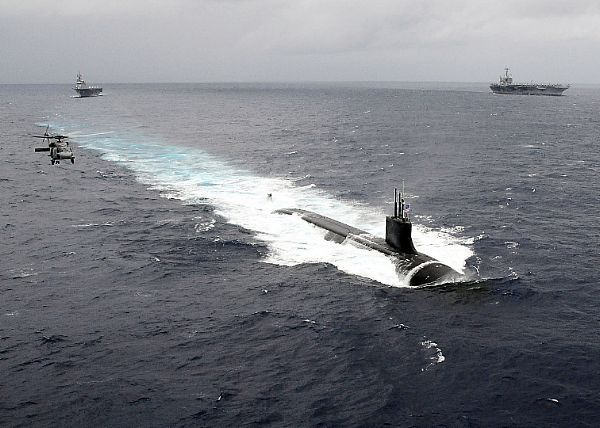 PACIFIC OCEAN (Nov. 17, 2009) The Seawolf-class attack submarine USS Connecticut (SSN 22) is underway in the Pacific Ocean with an HH-60H Sea Hawk helicopter from the Chargers of Helicopter Anti-Submarine Squadron (HS) 14. In the background are the aircraft carrier USS George Washington (CVN 73) and the Japan Maritime Self-Defense Force helicopter destroyer JS Hyuga (DDH 181)
