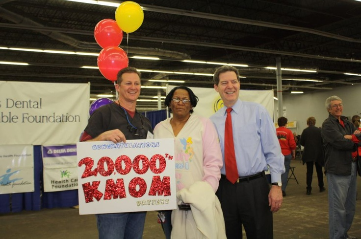 At KMOM Kansas City, we treated our 20,000th patient.  KDCF President Mark Herzog and Kansas Governor Sam Brownback recognized Roxie Brown.