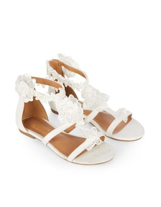 These beautiful sandals for girls are ornamented with lace flowers and faux pearls, and designed with zip fastenings on the heels. Flat, gripped soles provide a comfortable fit.